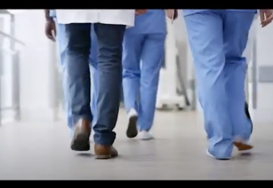 Image of doctors legs as they walk through the hospital